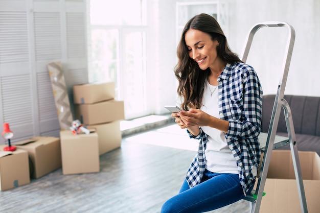 Verleidelijke donkerharige vrouw in een geruit hemd zit op de ladder in een ruim appartement te lachen en een mobiele telefoon in haar handen te houden