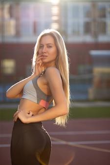 Verleidelijke fitte vrouw met getraind lichaam in sportkleding die zich voordeed op een tennisbaan in zonnestralen. vrouwelijk fitnessconcept