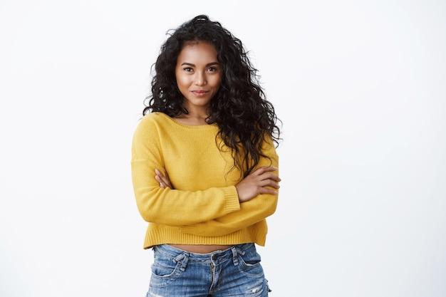 Verleidelijke jonge afro-amerikaanse vrouw met donker krullend kapsel, vastberaden en gemotiveerd glimlachen, zelfverzekerde pose met kruisarmen op de borst, lachende gedurfde camera, witte muur