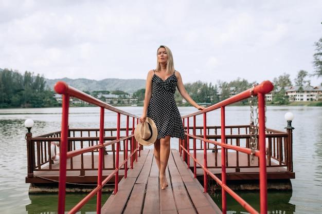 Verleidelijke jonge blonde in een zwarte jurk loopt pier en geniet van ontspannen. reizen en genieten