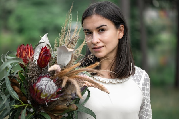 Verleidelijke jonge brunette vrouw in een witte jurk met een boeket bloemen in het bos op een wazige achtergrond,