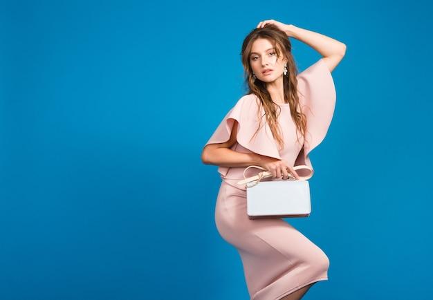Verleidelijke jonge stijlvolle sexy vrouw in roze luxe jurk, zomer modetrend, chique stijl, blauwe studio achtergrond, trendy handtas te houden