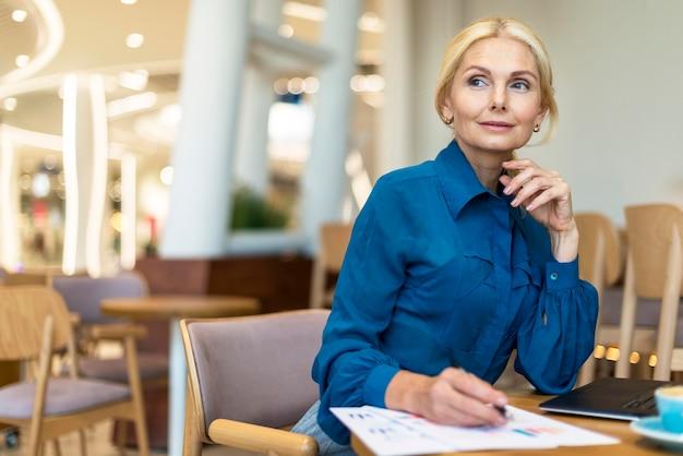 Verleidelijke oudere zakenvrouw omgaan met wat papier tijdens het werken op laptop