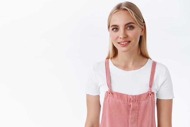 Verleidelijke, sensuele en vrouwelijke jonge blonde vrouw met blauwe ogen in trendy roze overalls, t-shirt, glimlachend, lief en koket, oprecht in de ogen kijkend, teder staande op een witte achtergrond