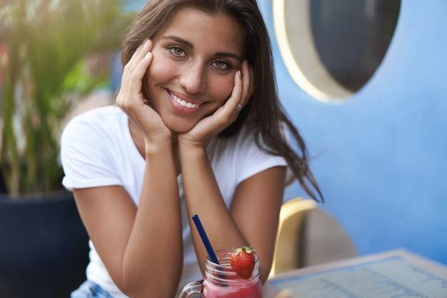 Verleidelijke sensuele jonge gelooide brunette vrouw zitten buiten straat