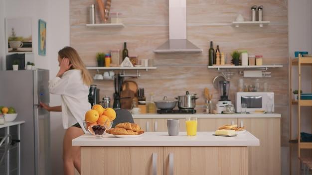 Verleidelijke vrouw die een heerlijk en gezond ontbijt bereidt met sexy zwart ondergoed. jonge aantrekkelijke blonde dame in lingerie en wit overhemd zitten in de ochtend in gezellige moderne keuken.