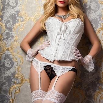 Verleidelijke vrouw met blond haar in een witte lingerie dichtbij de muur