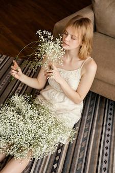 Verleidelijke vrouw poseren naast bank terwijl boeket van lentebloemen