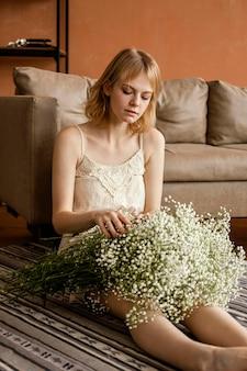 Verleidelijke vrouw poseren naast de bank terwijl ze boeket van delicate lentebloemen vasthoudt
