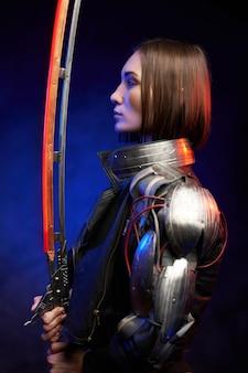 Verleidelijke vrouwelijke huurmoordenaar poseert op een donkere achtergrond en kijkt naar haar gloeiende zwaard. profiel van een militaire vrouw uit de toekomst in cyberpunkstijl.