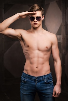 Verleiding soldaat. knappe jonge man die een zonnebril draagt en de hand op het voorhoofd houdt terwijl hij tegen een metalen achtergrond staat