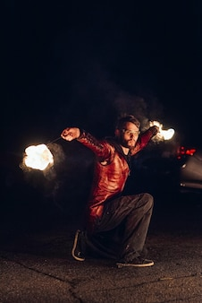 Verlicht de nachtelijke vuurshow met de deelname van de mensen, licht en open vuur Premium Foto