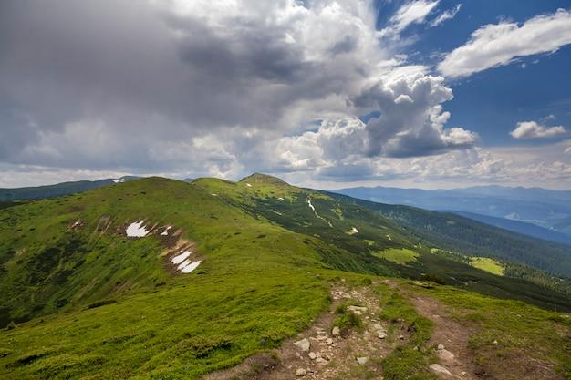 Verlicht door ochtendzon brede groene vallei, heuvels bedekt met bos en verre mistige bergen onder helderblauwe zomerhemel en witte gezwollen wolken