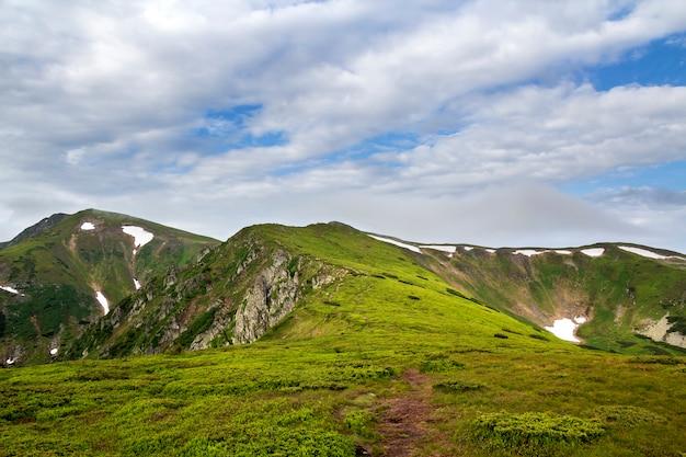 Verlicht door ochtendzon brede groene vallei, heuvels bedekt met gras en verre mistige bergrotsen onder een helderblauwe zomerhemel en witte gezwollen wolken
