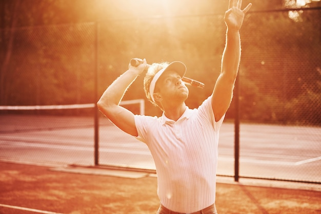 Verlicht door zonlicht. jonge tennisser in sportieve kleding is buiten op het veld.
