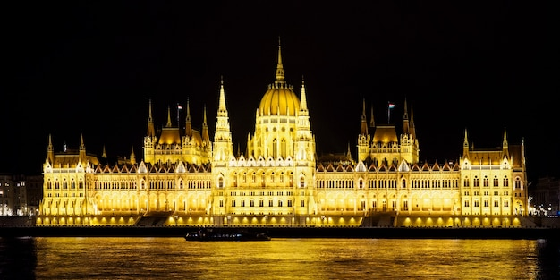 Verlicht hongaars parlement aan de rivieroever van de donau 's nachts in boedapest. reisbestemmingen.
