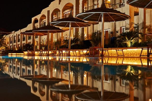 Verlicht hotel met zwembad 's nachts. avondlichten in het resort