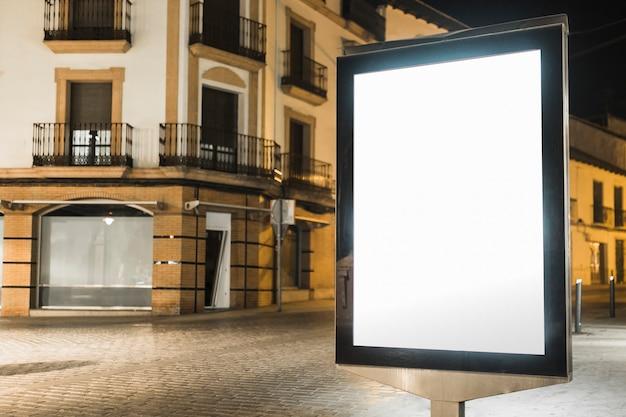 Verlicht lightboxaanplakbord dichtbij het flatgebouw