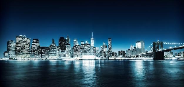 Verlichte brooklyn bridge en manhattan 's nachts