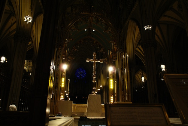 Verlichte christelijke kruis met zwarte achtergrond in een kerk.