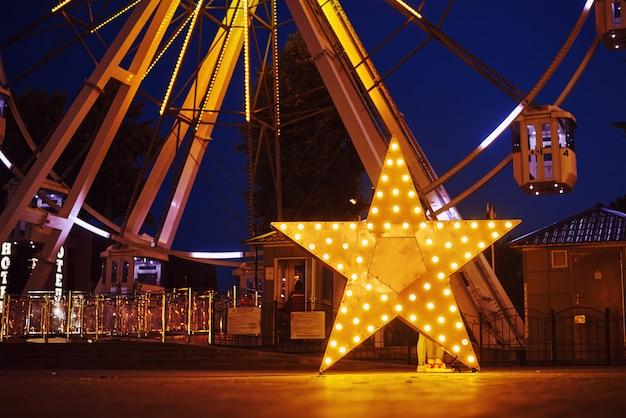 Verlichte gloeiende ster in pretpark bij nachtstad