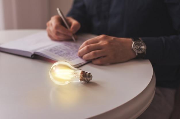 Verlichte gloeilamp ligt op een tafel in de buurt van een schrijven zakenman idee innovatie