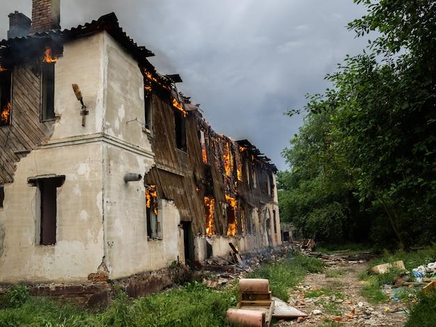Verlichte houten huis tussen de groene bossen. vlammen van vuur in de windows. gevaar voor het milieu