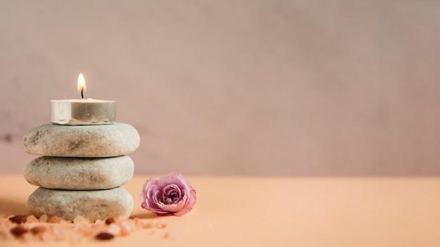 Verlichte kaars over de stapel spa stenen met himalayazouten en roze roos op gekleurde achtergrond