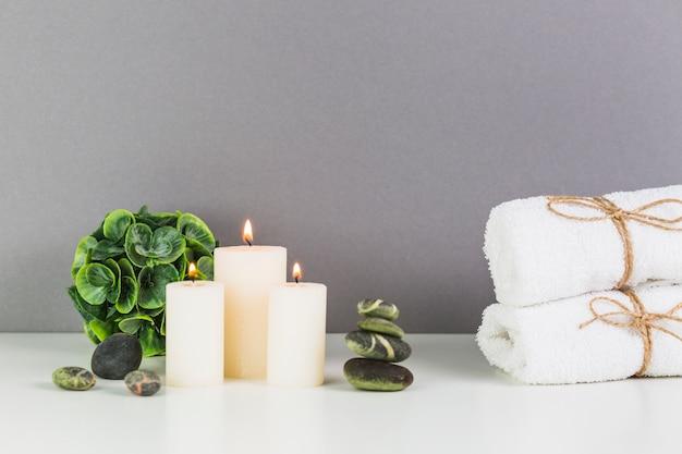 Verlichte kaarsen; handdoek en spa stenen op witte tafelblad