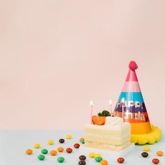 Verlichte kaarsen op cake; snoepjes en verjaardagshoed tegen gekleurde achtergrond