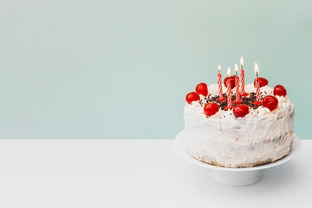 Verlichte kaarsen op verjaardagscake op caketribune tegen blauwe achtergrond