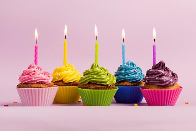 Verlichte kaarsen over de kleurrijke muffins tegen roze achtergrond