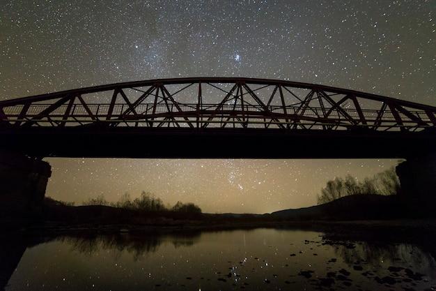 Verlichte metalen brug op betonnen steunen weerspiegeld in water op donkere sterrenhemel met melkweg sterrenbeeld achtergrond. nacht fotografie concept.