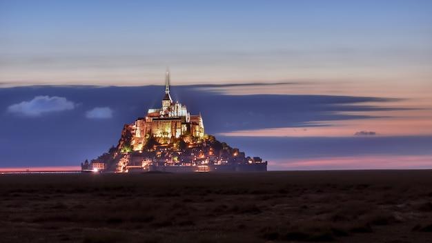 Verlichte mont saint michel in de schemering in een kleurrijke hemel