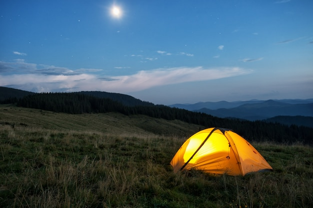 Verlichte oranje tent in bergen in de schemering