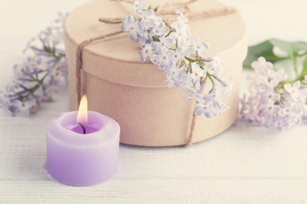 Verlichte paarse kaars en lila bloemen