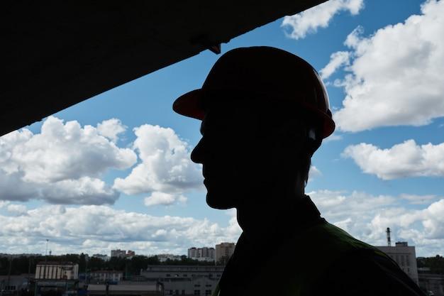 Verlichte profielweergave bij onherkenbare werknemer met veiligheidshelm tegen luchtkopieerruimte