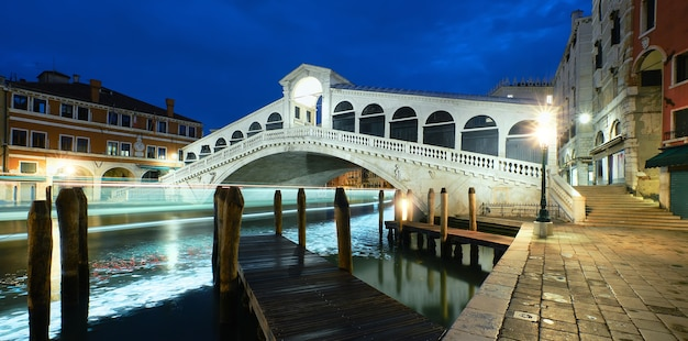 Verlichte rialtobrug over het canal grande in venetië, italië 's nachts. panoramisch beeld.