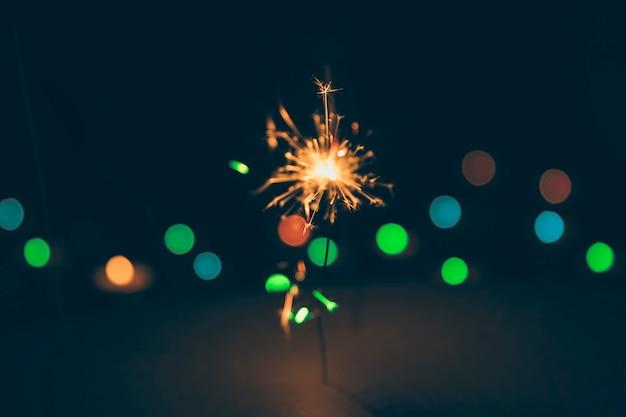 Verlichte sparkler op kleurrijke bokeh achtergrond