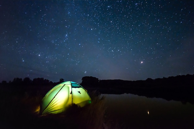 Verlichte tent bij de rivier en een prachtige hemel vol sterren