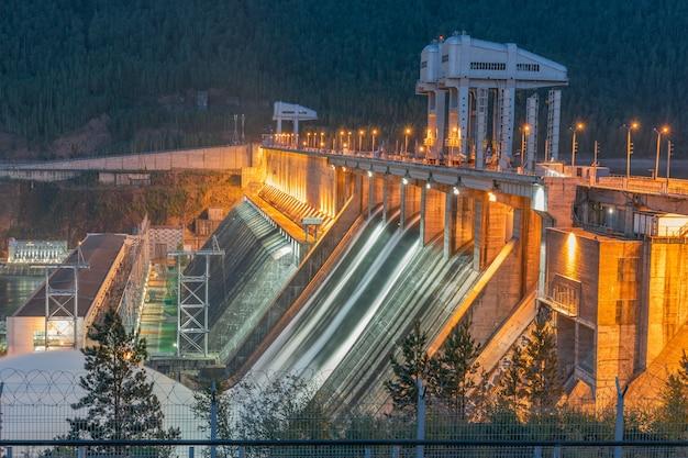 Verlichte waterkrachtcentrale achter prikkeldraad. waterafvoer.