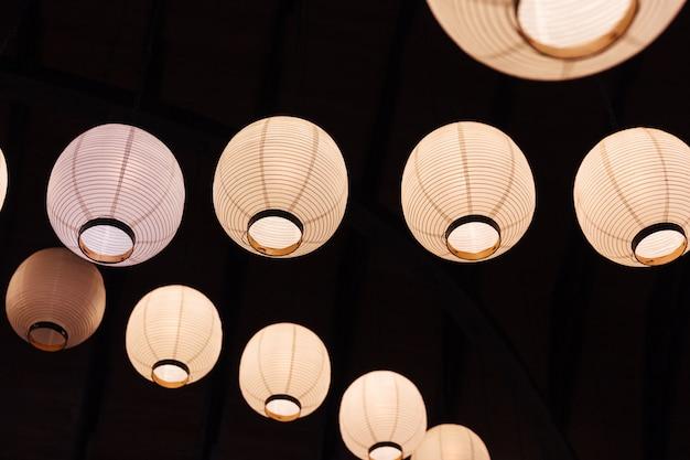 Verlichte witboeklampen op plafond op zwarte achtergrond.