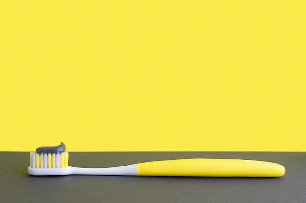 Verlichtende gele tandenborstel met tandpasta op ultieme grijze achtergrond. tandheelkunde concept. trend 2021.
