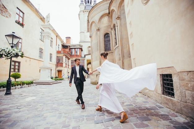 Verliefd bruidspaar, hand in hand, in een oude romantische stad
