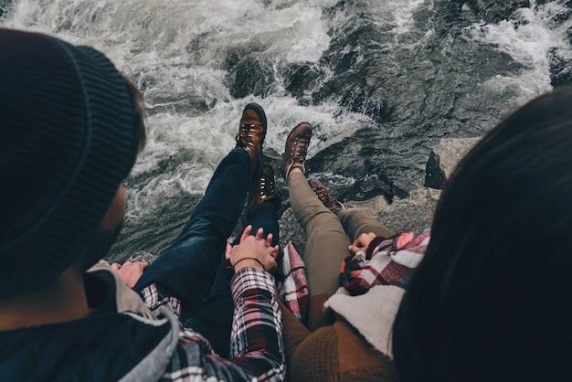 Verliefd. close-up bovenaanzicht van jong stel hand in hand zittend op de rotsen met de rivier eronder