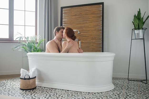 Verliefd. een man en een vrouw die samen in bad gaan, kussen en knuffelen