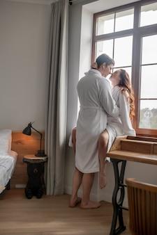 Verliefd. een man en een vrouw in witte badjassen die bij het raam staan en verliefd zijn