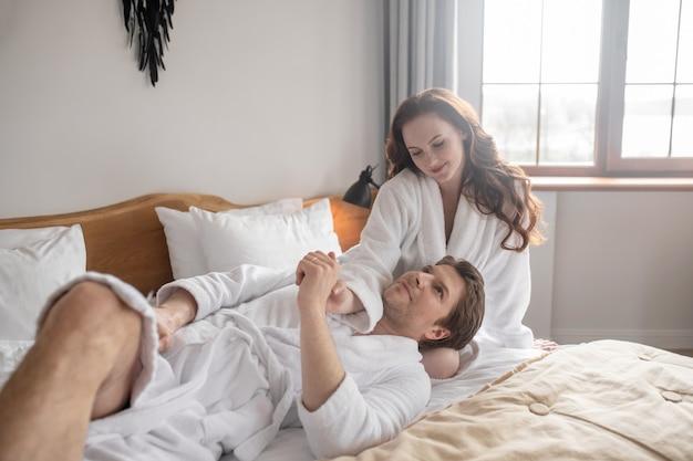 Verliefd. een stel in witte badjassen liggend op het bed en verliefd
