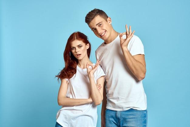 Verliefd man en vrouw in spijkerbroek en een t-shirt op een blauwe knuffel elkaar en veel plezier