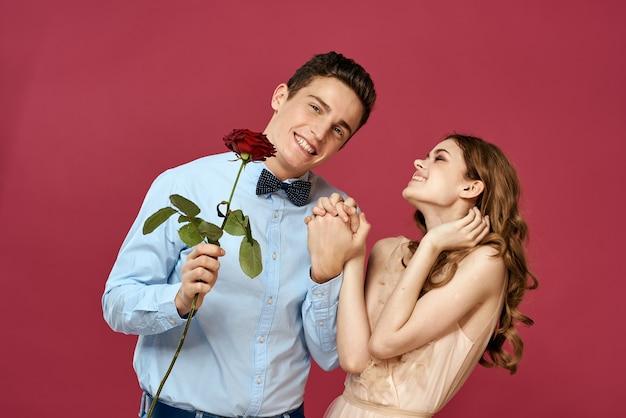Verliefd man en vrouw met een rode bloem op een roze